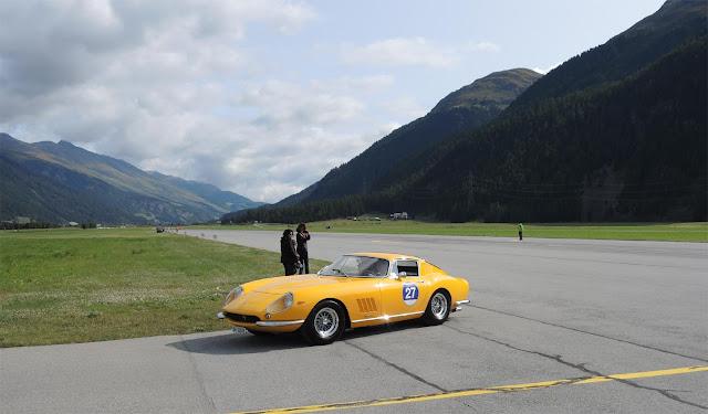 Gelber Ferrari 275 GTB bei  Fahrprüfung auf Flugbahn des Airport Engadin, Berge und Wiesen im Hintergrund