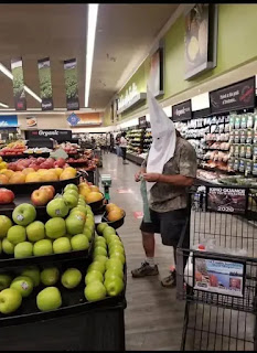 Hombre con capirote de semana Santa en el supermercado
