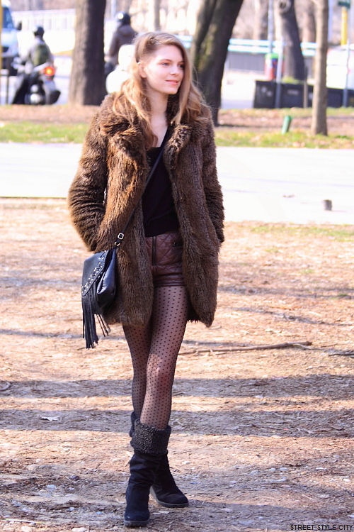 Beautiful girl wearing leather shorts,pantyhose,boots and faux fur in the streets of Milan. Street style fashion outfit.