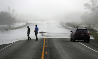 Motorists watch as flood waters from the Guadalupe river spill over a Texas highway. (Photograph Credit: Eric Gay/AP) Click to Enlarge.