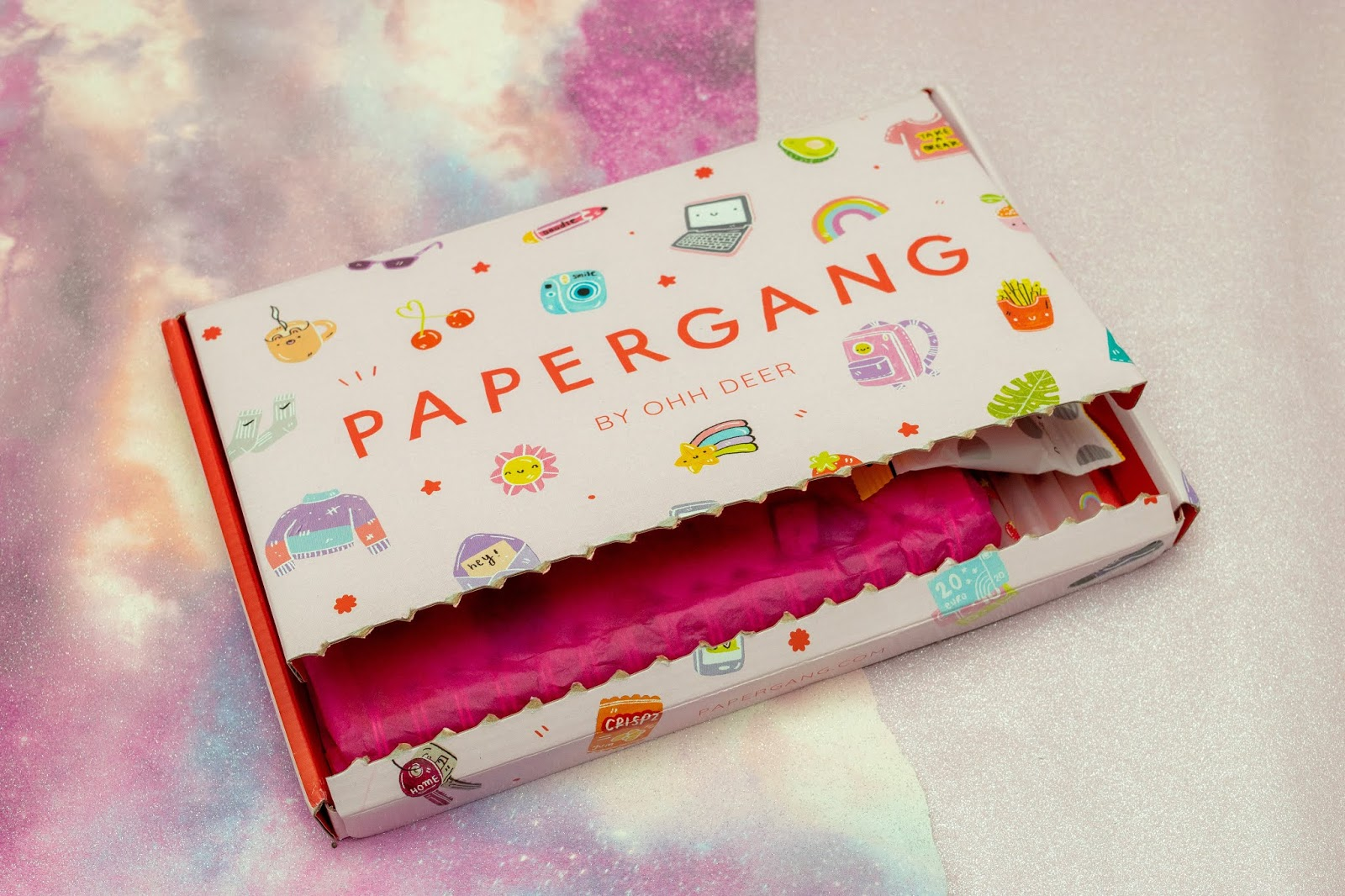 A letterbox size pink box with doodles all over and the papergang on the front.