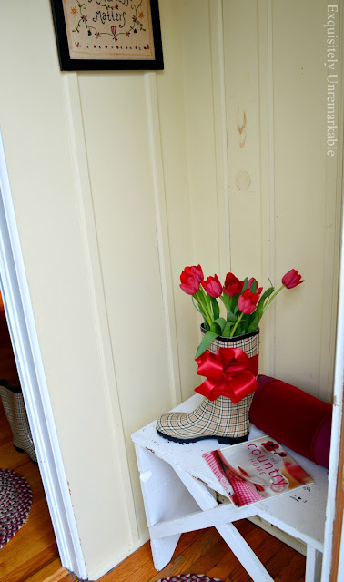 Tulips in a rain boot on bench in mudroom