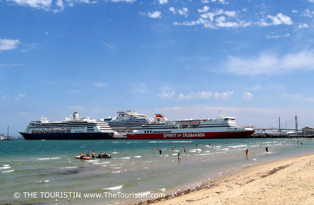 People swimming on a white sandy beach with three large passenger ferries in the background.