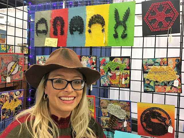 Jessica Greer standing by her string artwork inspired by Bob's Burgers.