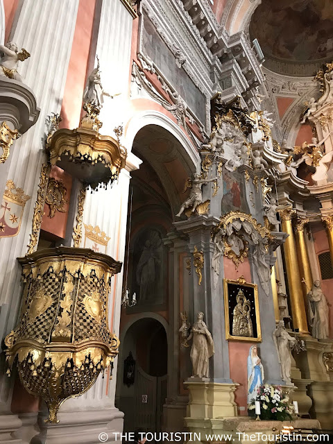 Golden pulpit and pastel coloured interior of the Saint Theresa church in Vilnius in Lithuania