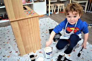 boy painting play kitchen