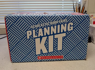 Blue-cardboard box, labeled 'Scholastic Book Fairs Planning Kit,' sitting on counter-top