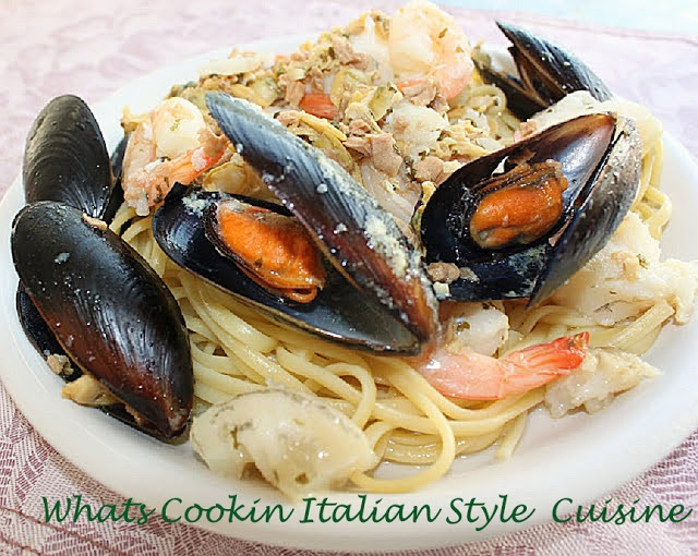 This is a white clam sauce with assorted seafood on top of pasta on a large white plate and the mussels are all open on top