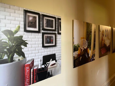 4 large blown up photos of 1/12 scale modern miniature scenes on display on a wall.
