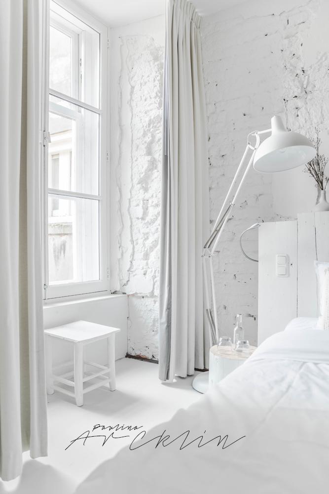 Bonito detalle del taburete blanco cerca de la ventana de la habitación