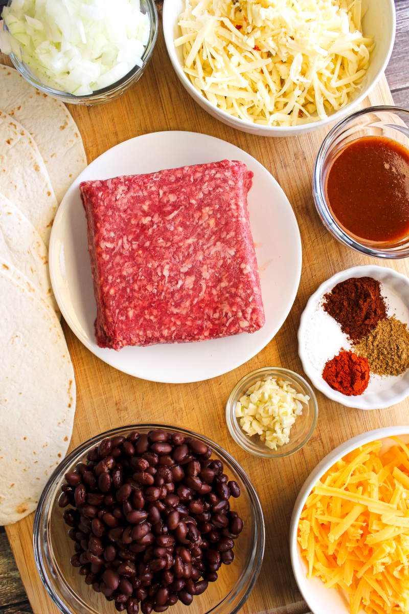 Top view of beef and bean ingredients on a wooden cutting board.