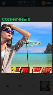 Девушка в солнечных очках на курорте смотрит вдаль на берегу