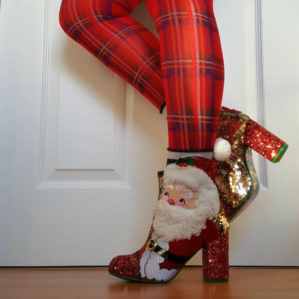 standing wearing tartan tights and Santa Claus ankle boot with back leg lifted