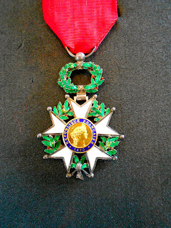 A white and green medal on a red ribbon.