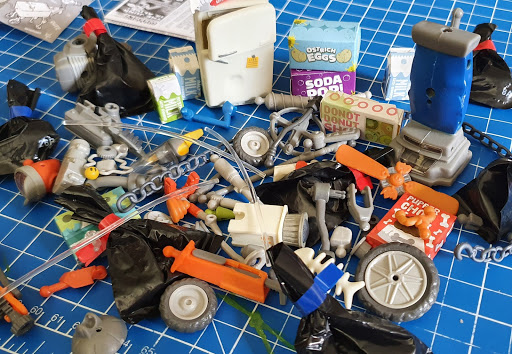 Entire contents of Hexbug Trash Bot Dumpster strewn on table