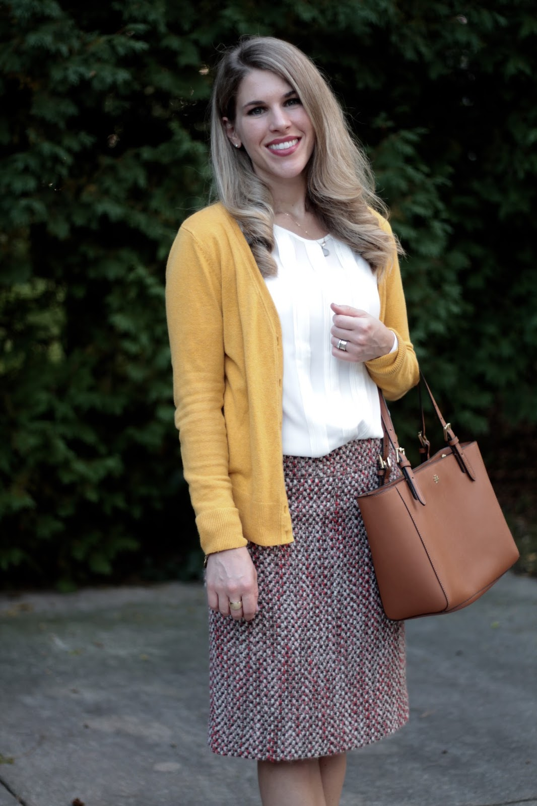 yellow mustard cardigan, white blouse, J.Crew pink boucle pencil skirt, cognac wedges, Tory Burch tote