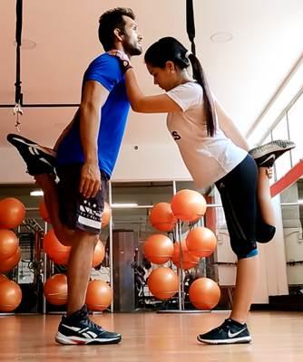 Ejercicio en parejas para estirar los músculos de la zona anterior de los muslos (cuadriceps)