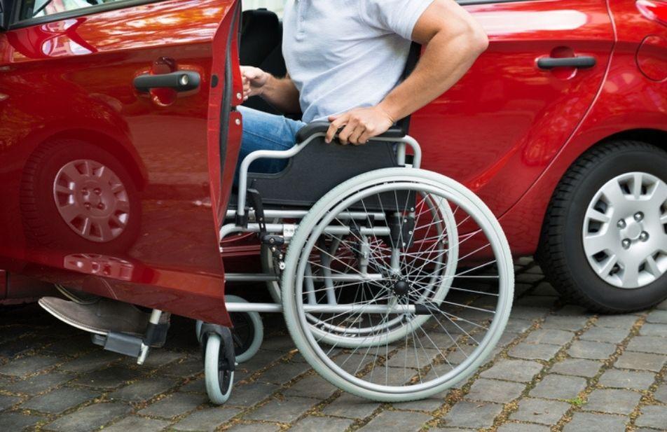 A imagem mostra um carro vermelho com a porta aberta, junto a porta um cadeirante.