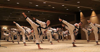 Many martial arts black belts doing a synchronized side kick
