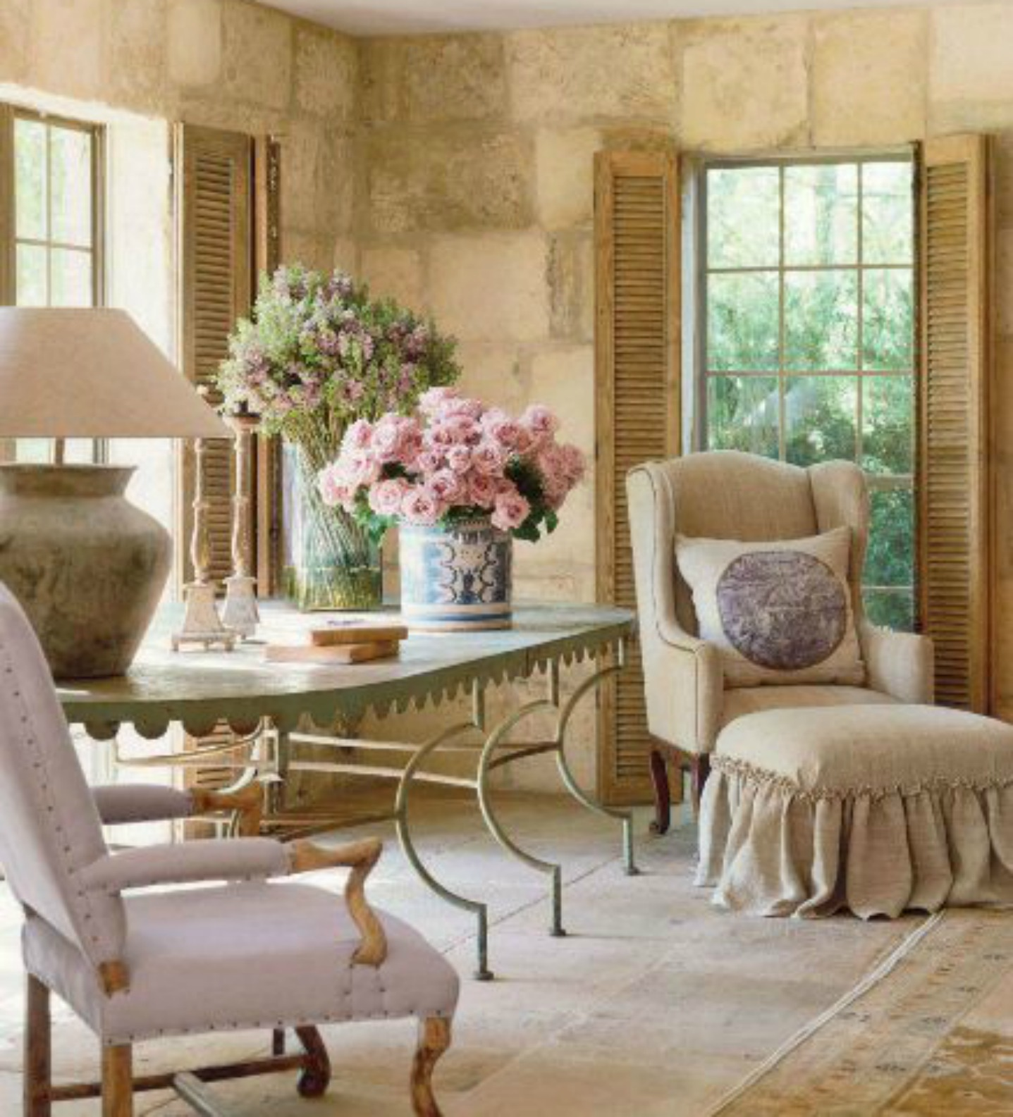 French farmhouse living room with antiques, limestone, and shutters. Design by Pamela Pierce. #chateaudomingue #frenchcountry #reclaimedstone