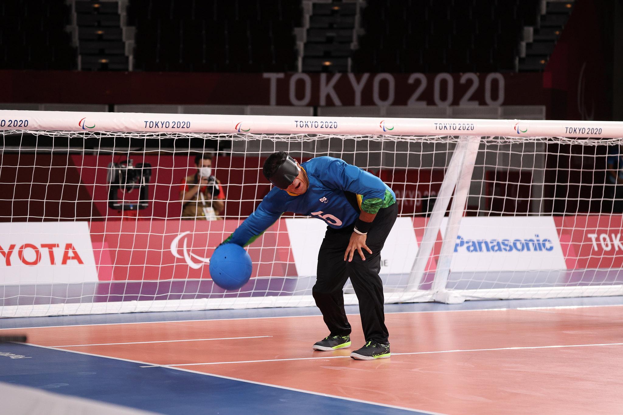 Parazinho arremessa uma bola azul em direção ao gol adversário