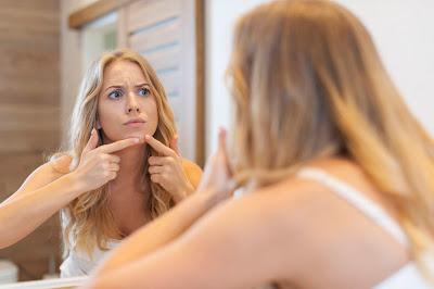 Mujer con un grano en el rostro