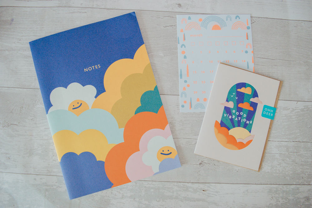 A large notebook, a greeting card and a calendar card laid out flat
