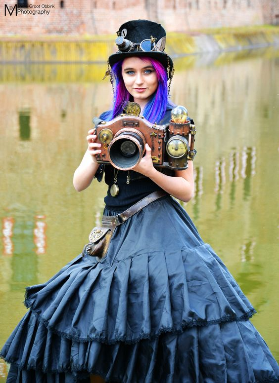 Woman with blue, pink and purple hair, holding a steampunk camera wearing a top hat, skirt and goggles. women's steampunk costumes and clothing
