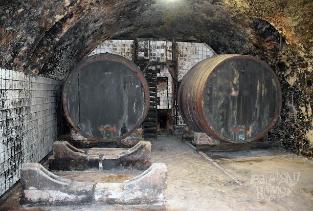 Fa hordók az előtérben, hártébb fehér csempés, falba épített bortároló.