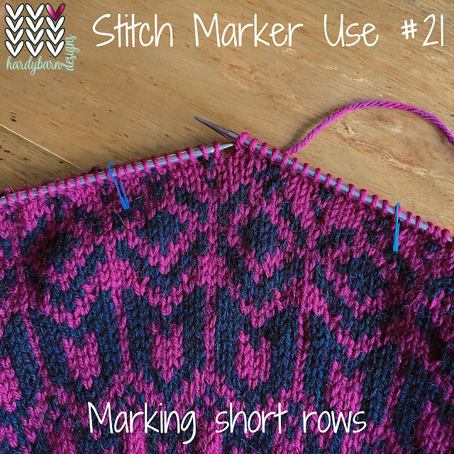magenta and navy stranded knitting on needles with stitch markers