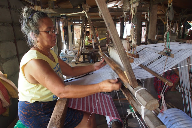 old lady weaving binakul textile in three-pedal loom