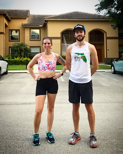 Ali and Matt standing in a parking lot, smiling after a hard run