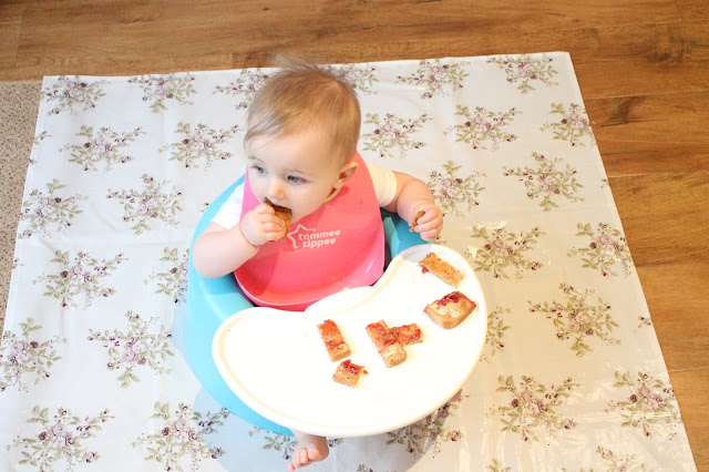 baby sat in bumbo eating jam on toast with floor protector