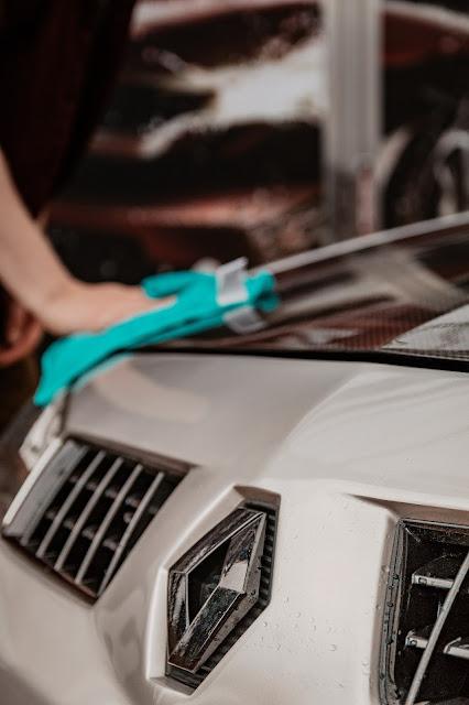 Person polishing car:  Photo by Adrian Dascal on Unsplash