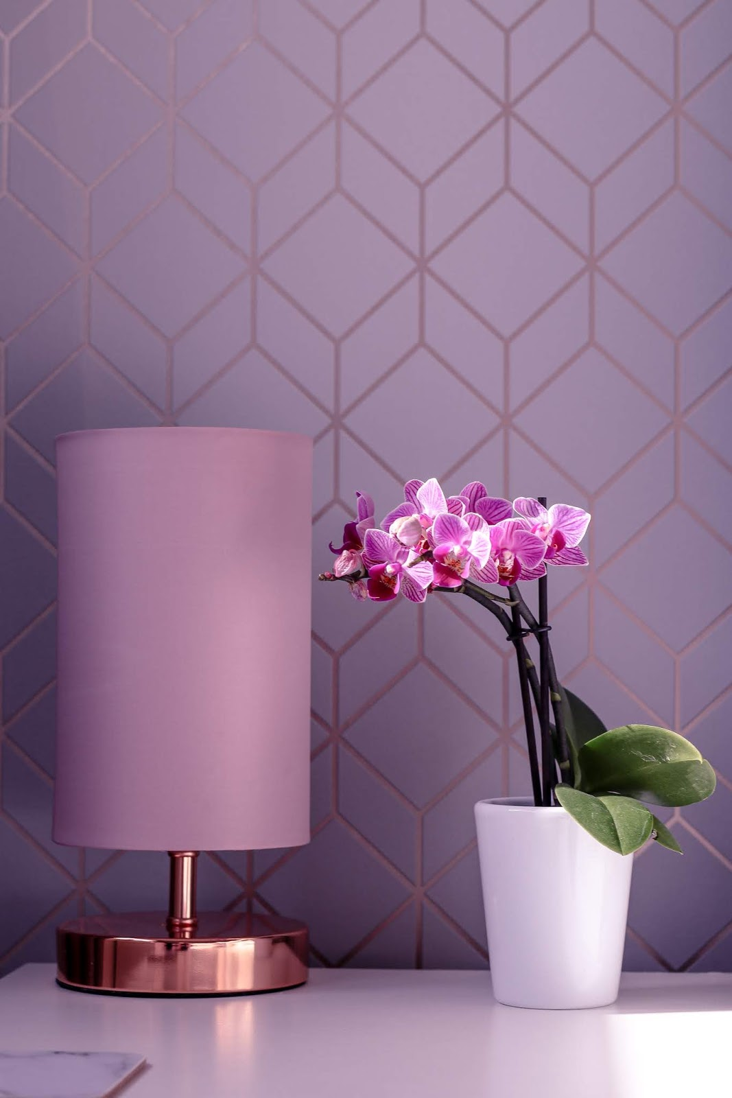 Close up photo of a purple orchid on a white bedside table next to a pink lamp