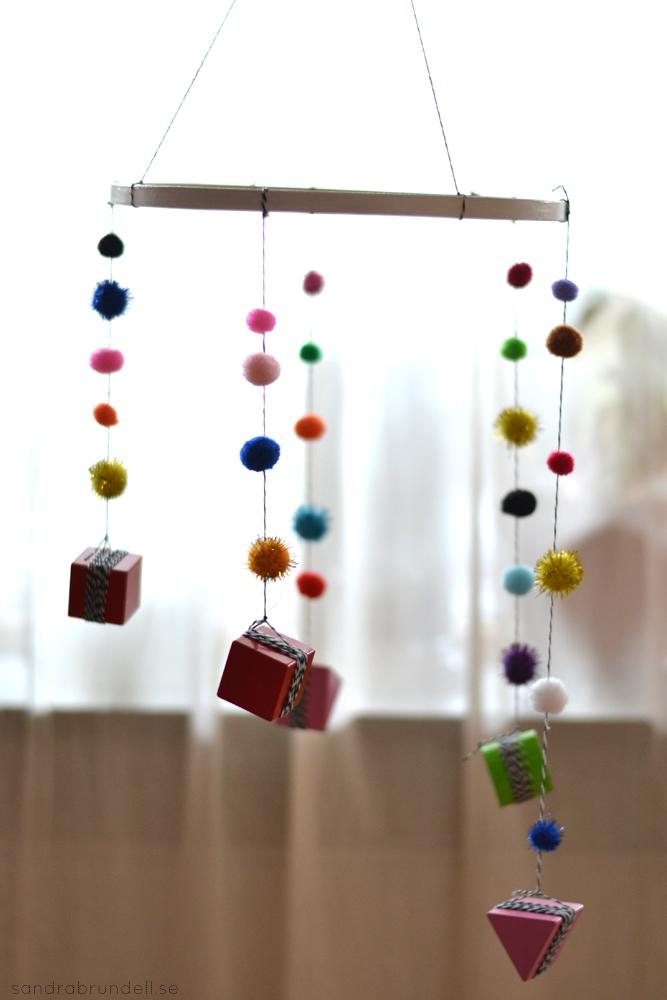 Gör en egen mobil till spjälsängen av klossar och färgglada bollar.