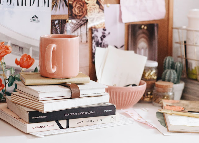 The image shows a pile of stacked books on a white desk. In the background are pink coloured bowls and glass jars.