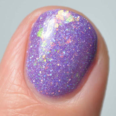 purple nail polish with flakies close up swatch