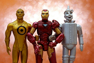 lose-up of three elemental-themed figures: Gold of the Metal Men, Iron Man of the Avengers, and the Tin Man from the Land of Oz.