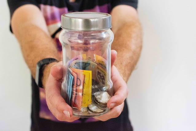 person holding jar of different kinds of money