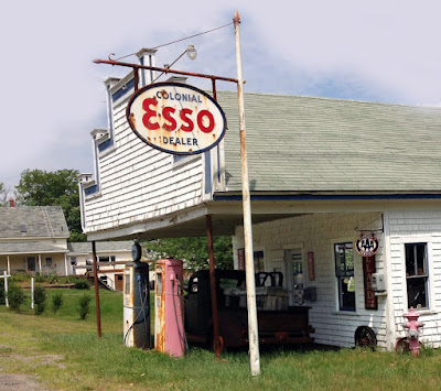 Exterior of old gasoline station, with old pumps and pickup truck.