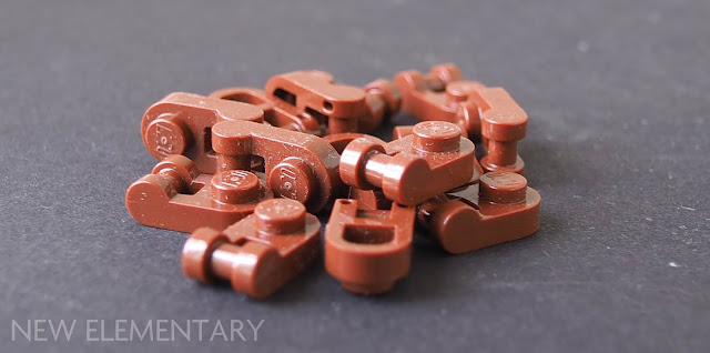 LEGO Part 26047, Plate 1 x 1 Rounded with Handle. A photograph of a small pile of Reddish Brown ones.