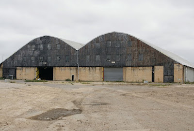 Exterior photograph of the warehouse. The view of the buildling is similar to that in the photograph above, but there is no road leading up to the building: instead, the foreground shows bare earth.