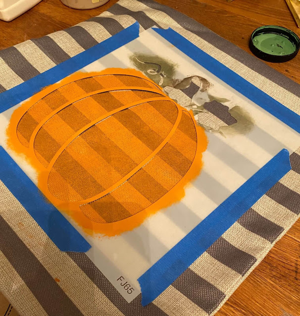Photo of a pumpkin stencil being applied to a pillow cover.