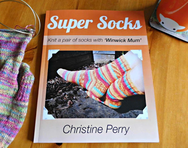 An orange Super Socks book lies on a wooden table. To the left is partly-knitted pink striped sock and to the right is an orange mug of tea