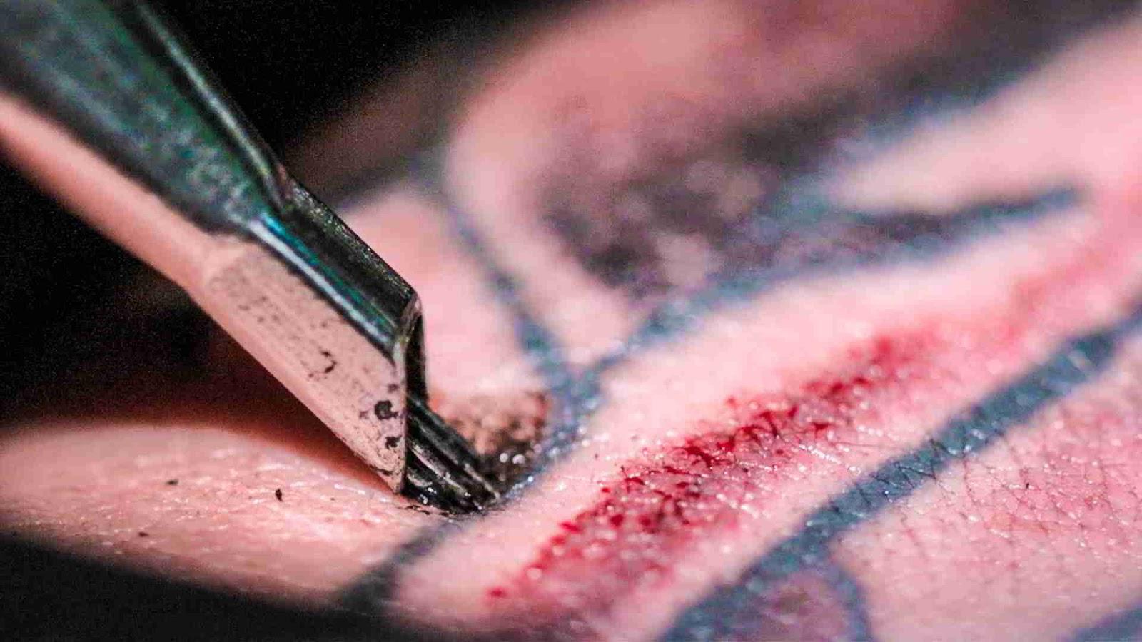 primer plano de una aguja de tatuaje penetrando en la piel