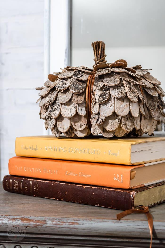 rustic pumpkin on stack of vintage books