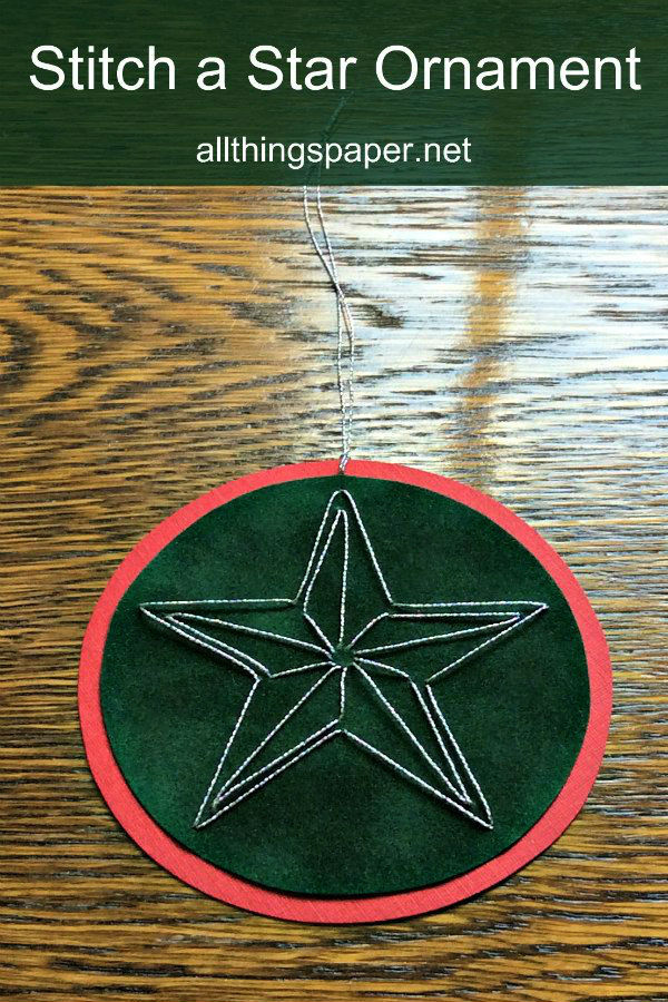 embroidered silver star on circular layered paper ornament displayed on table