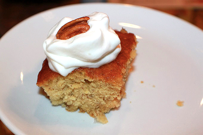 this is a slice of fresh apple cake with cream and pecans on top
