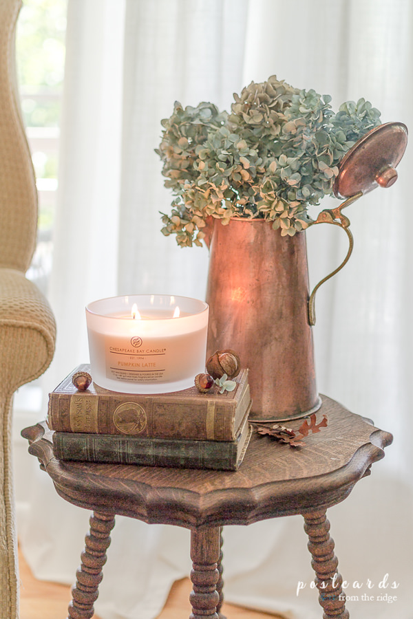 copper pitcher with dried hydrangeas and old books